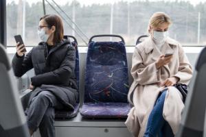 Personas en autobús con mascarilla y móvil
