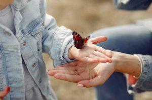 Niña con mariposa en la mano