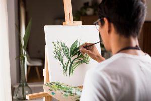 Hombre dedicando tiempo para sí mismo pintando un cuadro como propósito saludable para el 2021