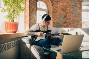 Joven estudiando música para pasar el tiempo en casa