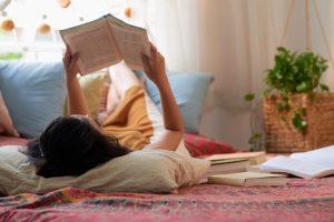 Joven leyendo para pasar el tiempo en casa