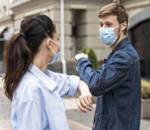 Jóvenes saludándose con el codo tras pandemia de coronavirus